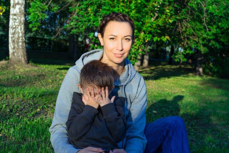 Mãe e filho que sentam-se na grama no parque imagem de stock royalty free