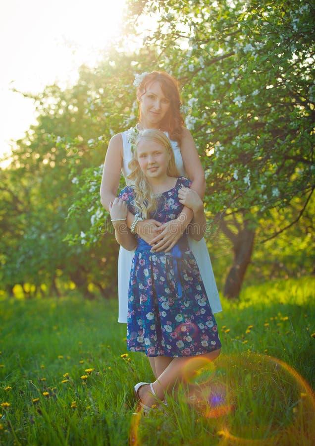 A mãe e a menina bonita da criança na flor jardinam imagens de stock royalty free