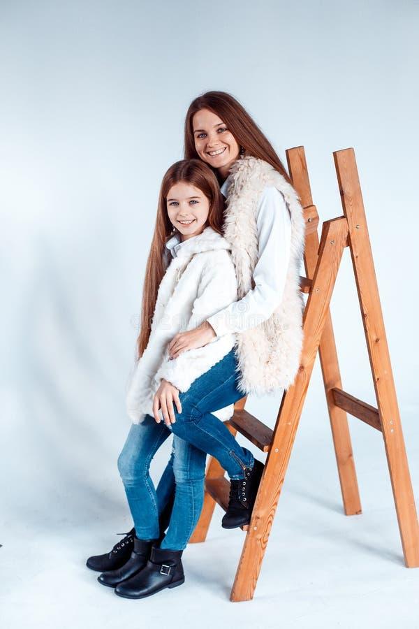 Mãe e menina bonitas à moda no estúdio que tem o divertimento meninas que sentam-se na escada de madeira fotografia de stock royalty free