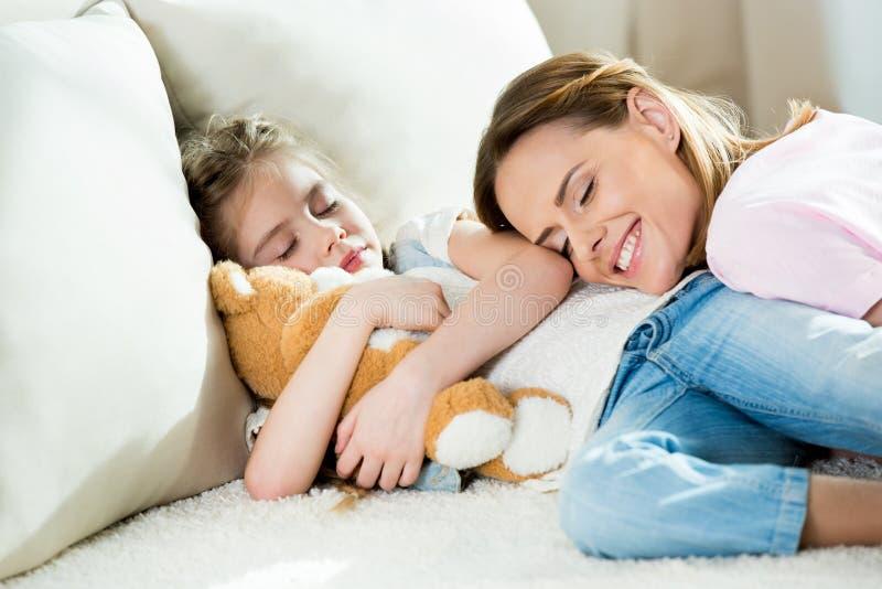 Mãe e menina bonito com sono do urso de peluche foto de stock