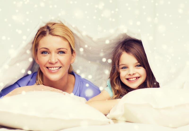 Mãe e menina felizes sob a cobertura em casa fotografia de stock