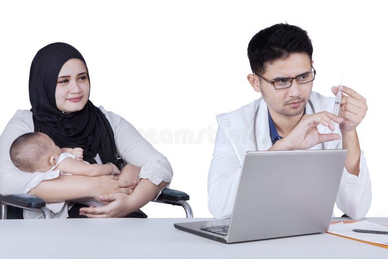 A mãe e o bebê com doutor guardam a seringa fotos de stock royalty free