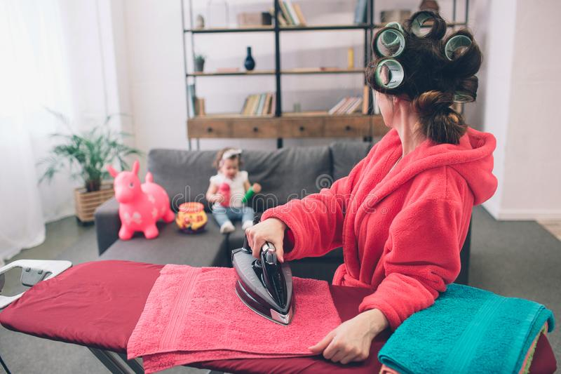A mãe e o bebê contrataram junto na roupa passando dos trabalhos domésticos Dona de casa e criança que fazem trabalhos de casa Mu imagens de stock