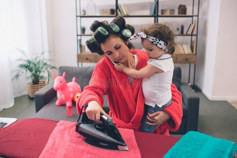 A mãe e o bebê contrataram junto na roupa passando dos trabalhos domésticos Dona de casa e criança que fazem trabalhos de casa Mu fotografia de stock