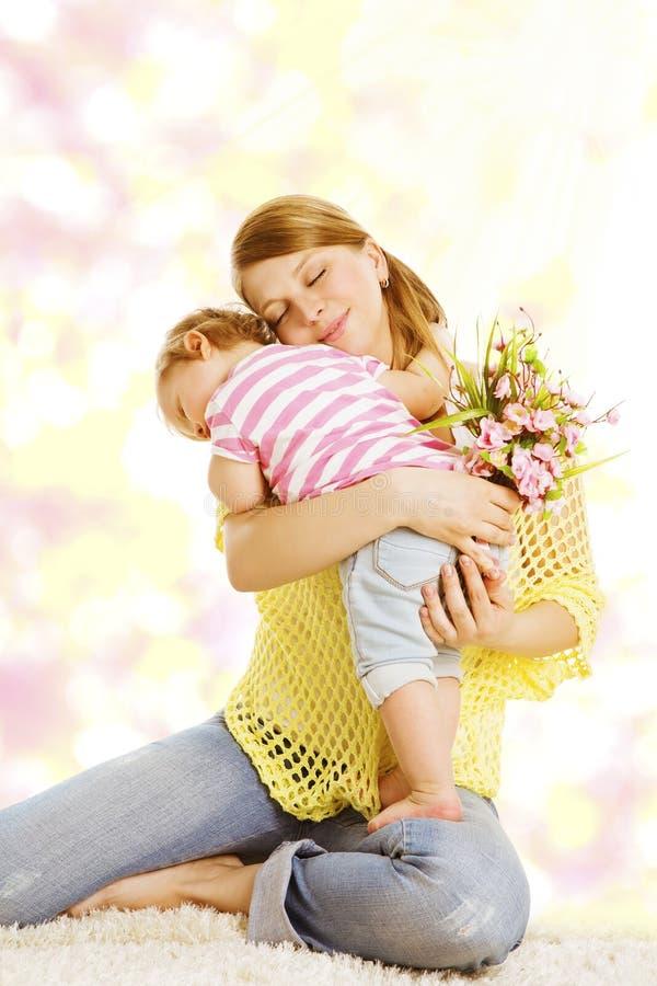 A mãe e o bebê dão o presente do ramalhete da flor, a menina feliz da mamã e da criança foto de stock royalty free