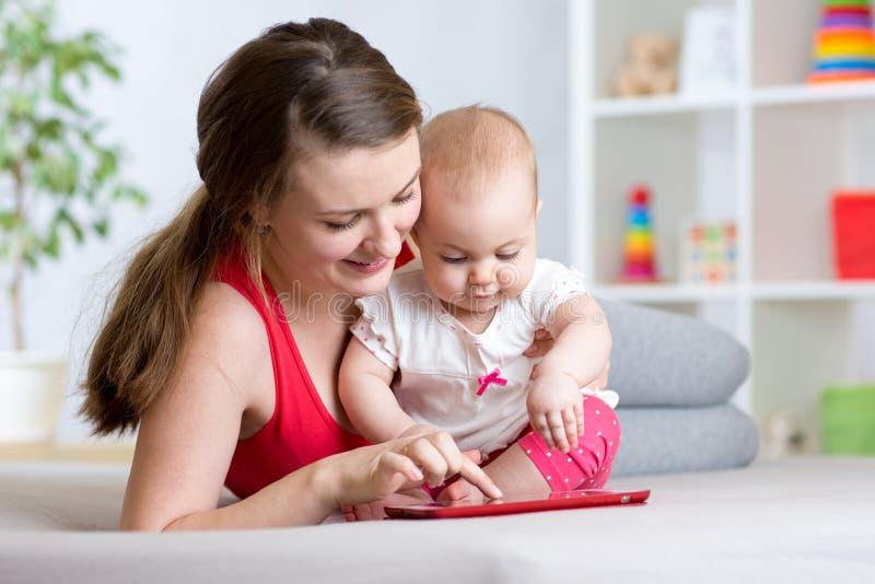 A mãe e o bebê estão olhando para jogar em casa o tablet pc no sofá imagem de stock