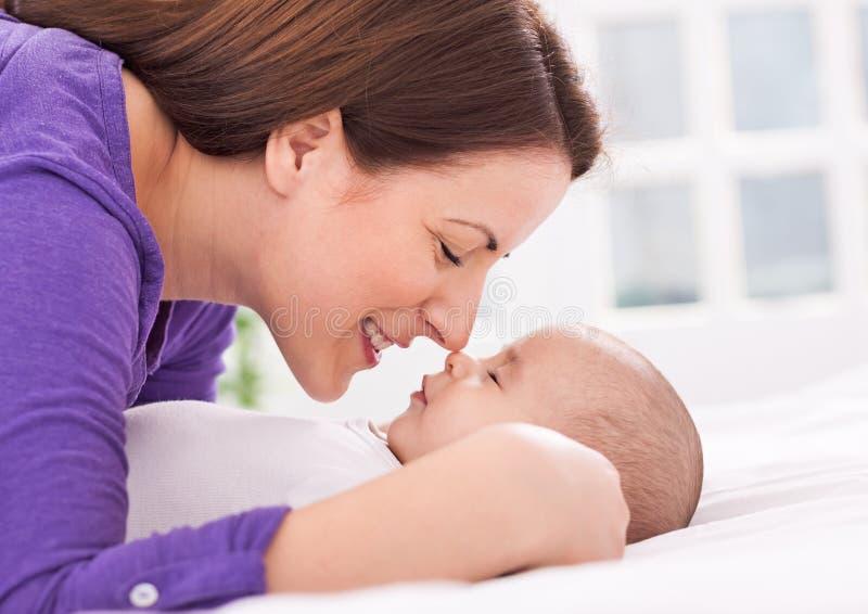 A mãe e o bebê novos bonitos estão tocando delicadamente nos narizes foto de stock royalty free