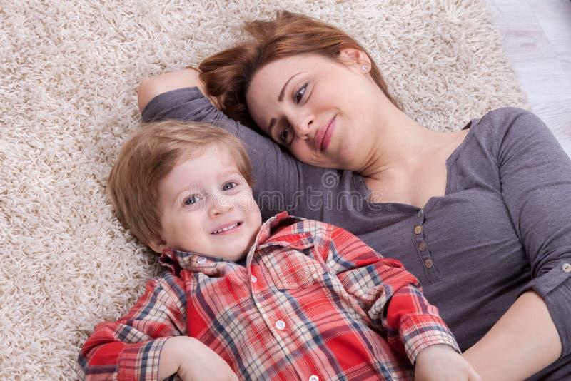 A mãe e o filho apreciam e riem fotografia de stock