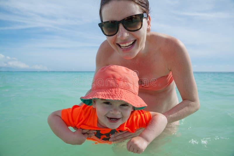 A mãe e o filho apreciam o dia na praia tropical imagens de stock royalty free