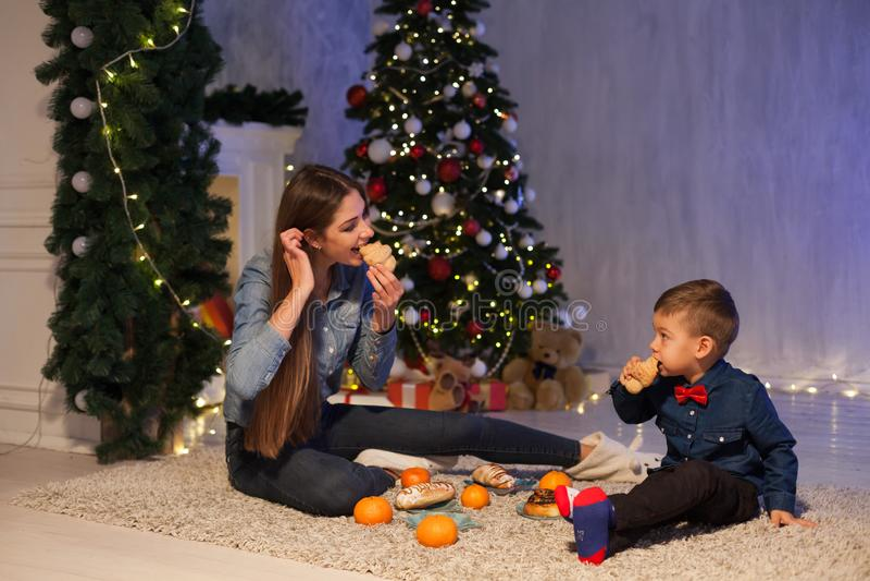 A mãe e o filho comem a árvore de Natal do ano novo das tangerinas imagens de stock royalty free