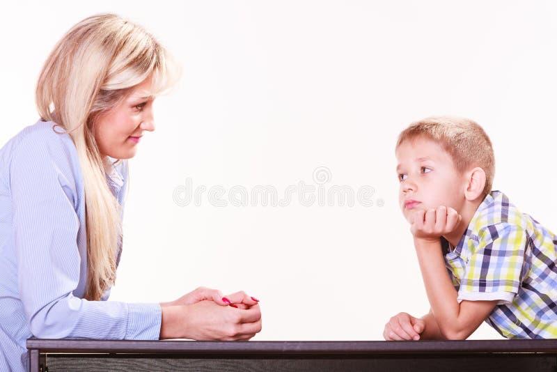 A mãe e o filho falam e discutem sentam-se na tabela imagens de stock royalty free