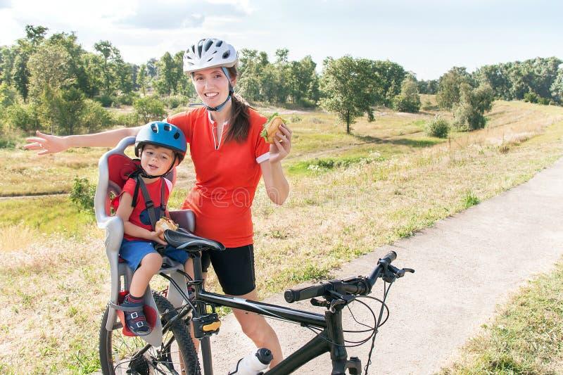 A mãe e o filho felizes estão comendo o almoço (petisco) durante o passeio da bicicleta fotos de stock royalty free