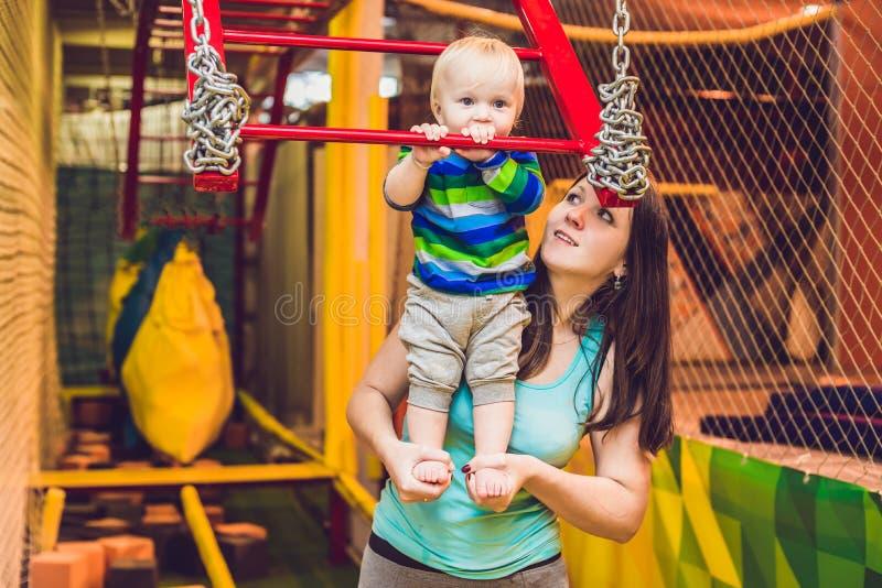 A mãe e o filho passam o curso de obstáculo no clube desportivo fotografia de stock royalty free