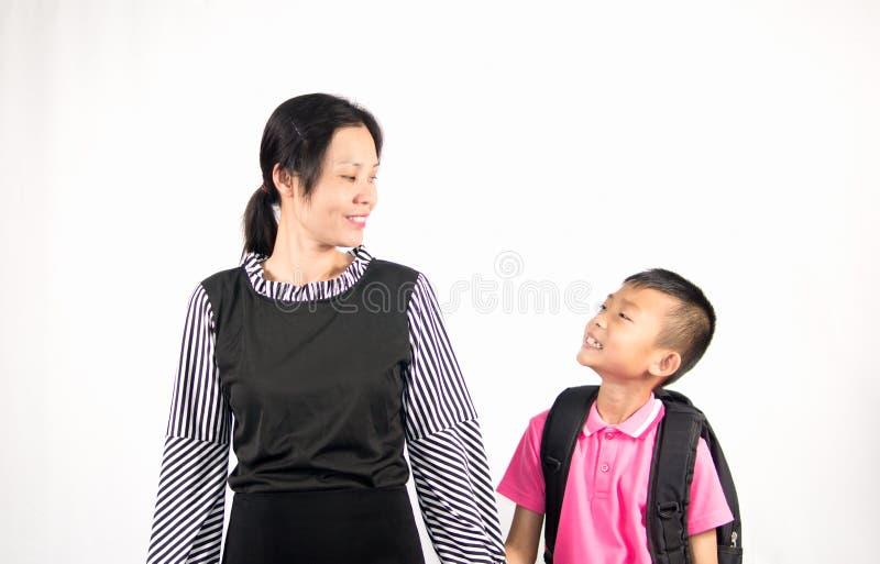 A mãe e o filho que sorriem, filho são estudante no fundo branco imagens de stock