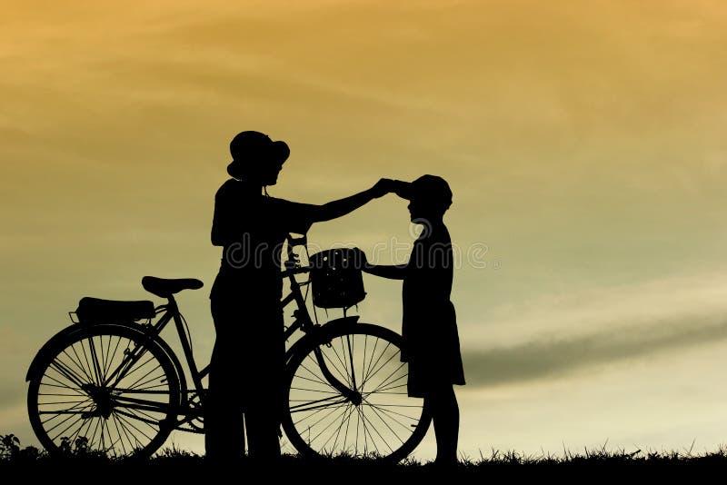 A mãe e o filho que têm a bicicleta da equitação do divertimento no por do sol, mostram em silhueta uma criança no por do sol, fotos de stock
