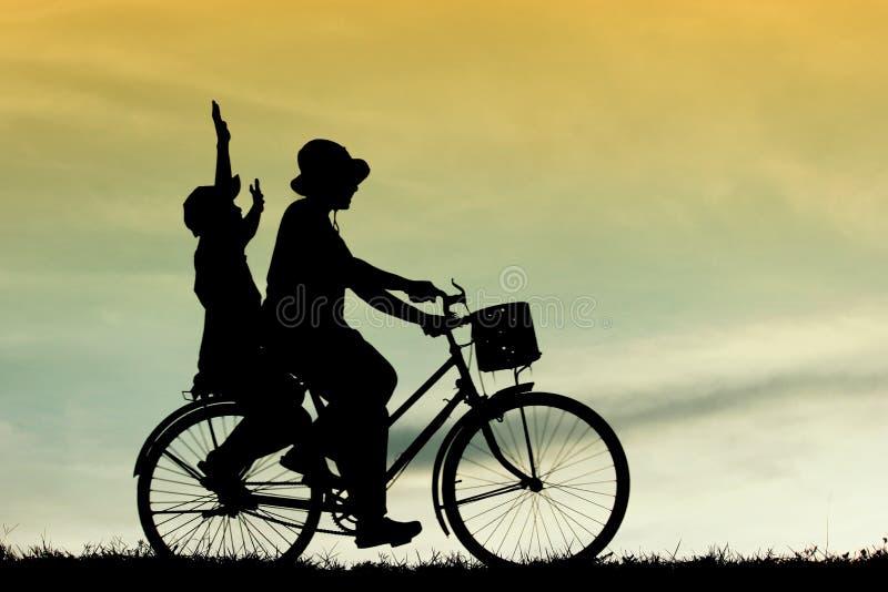 A mãe e o filho que têm a bicicleta da equitação do divertimento no por do sol, mostram em silhueta uma criança no por do sol, fotos de stock royalty free