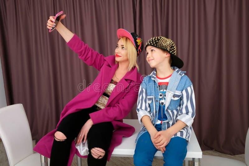 A mãe e o filho tentam sobre a roupa e o divertimento ter em casa fotos de stock