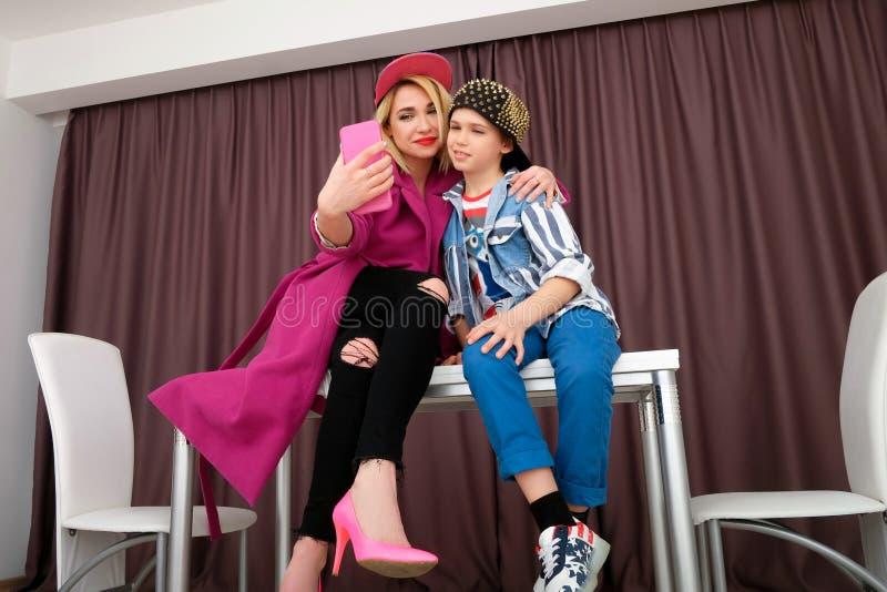 A mãe e o filho tentam sobre a roupa e o divertimento ter em casa fotografia de stock royalty free