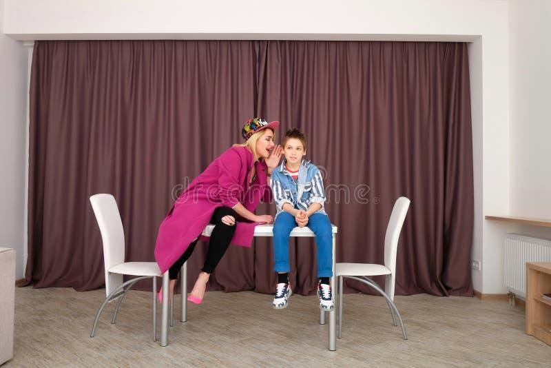 A mãe e o filho tentam sobre a roupa e o divertimento ter em casa imagens de stock