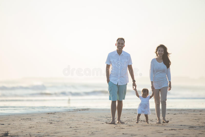 A mãe e o pai estão ensinando suas caminhadas da filha na praia fotos de stock royalty free