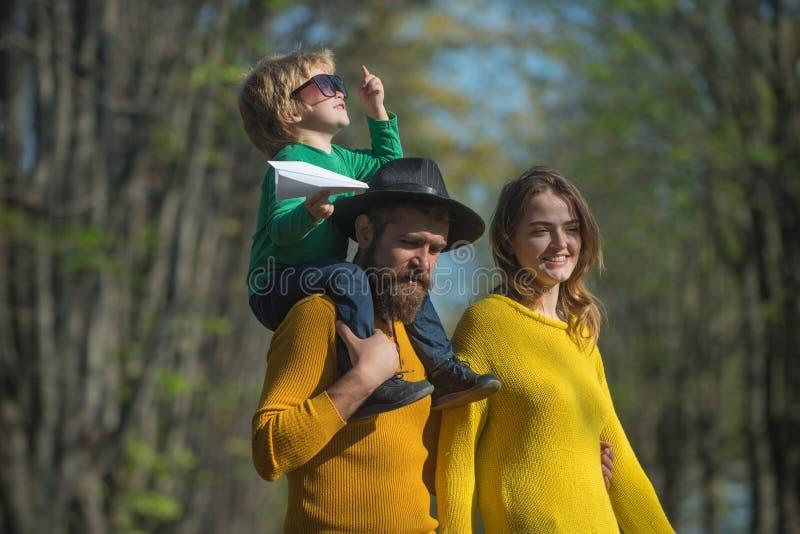 A mãe e o pai que rebocam a criança pequena sentem livres no ar fresco A família feliz passa o tempo livre junto A liberdade é imagem de stock royalty free