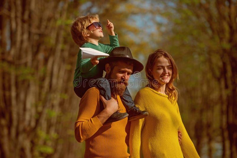 A mãe e o pai que rebocam a criança pequena sentem livres no ar fresco A família feliz passa o tempo livre junto A liberdade é fotografia de stock royalty free