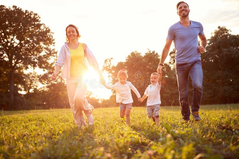 Mãe e pai com as crianças que correm na natureza fotografia de stock royalty free