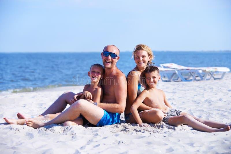 Mãe e pai de sorriso com as crianças na praia imagem de stock