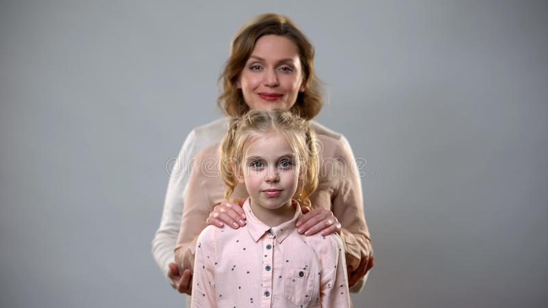 Mãe e pai que abraçam a menina, o apoio fêmea e o cuidado, família da educação da criança fotografia de stock royalty free