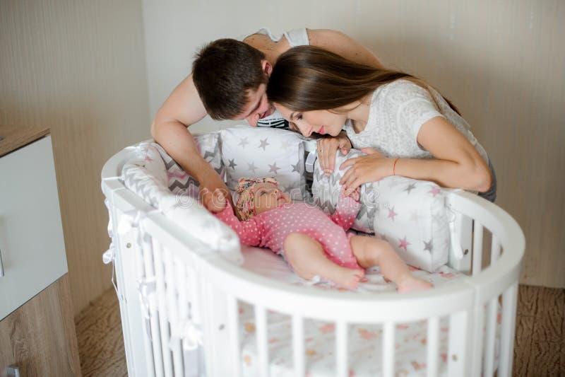 Mãe e pai que olham em sua menina no romper cor-de-rosa na cama imagem de stock royalty free