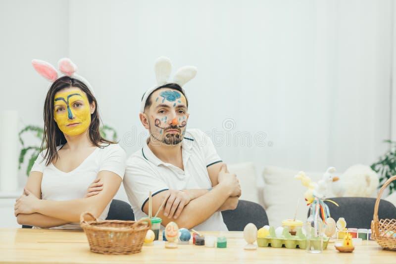 Mãe e pai que sentam-se de volta à parte traseira, olhando fresco e seguro Suas caras são pintadas, as mãos dobradas foolish imagens de stock