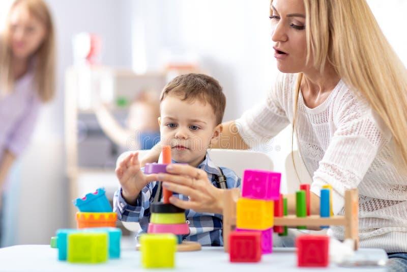 Mãe e seu filho construindo uma torre pirâmide de brinquedos fotografia de stock royalty free