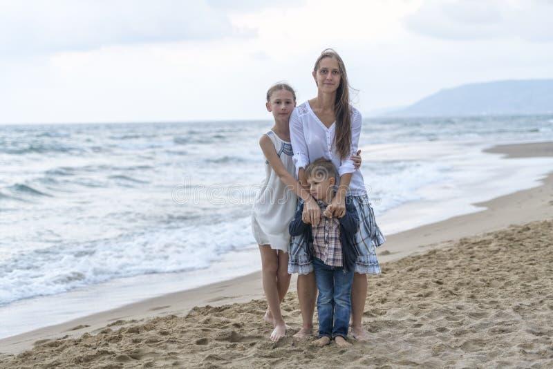 mãe e seus filha e filho na praia imagens de stock