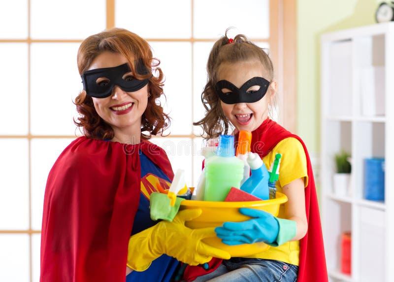 Mãe e sua criança no traje do super-herói Mum e criança prontos para abrigar a limpeza Houseworking e tarefas domésticas foto de stock royalty free