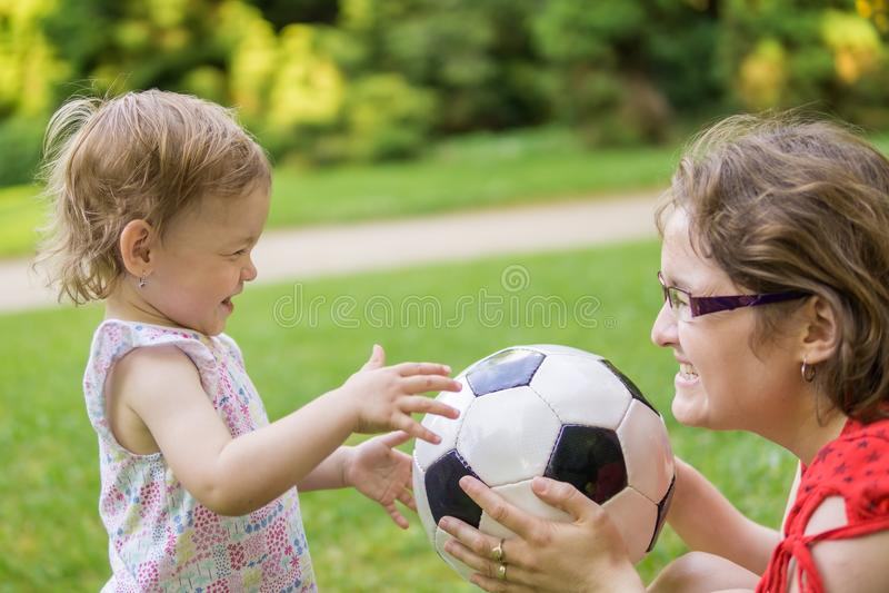 A mãe e sua filha estão jogando com a bola do futebol no parque imagens de stock royalty free