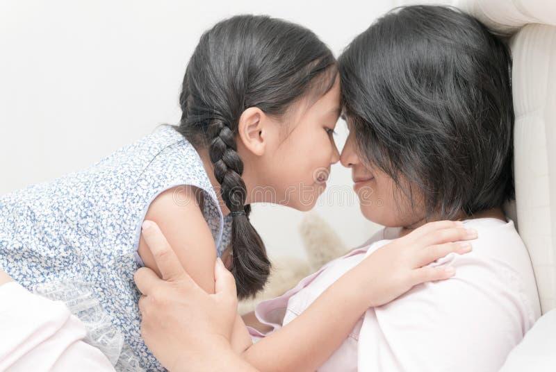 A mãe e sua filha estão tocando em no seus narizes e sorriso, fotografia de stock royalty free