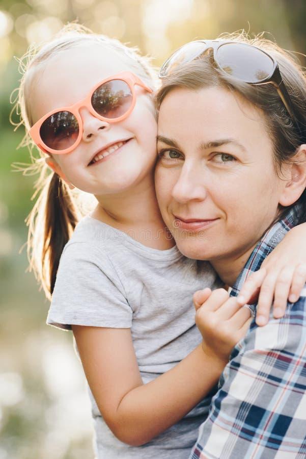A mãe e sua filha pequena encantador estão abraçando e estão sorrindo imagem de stock royalty free