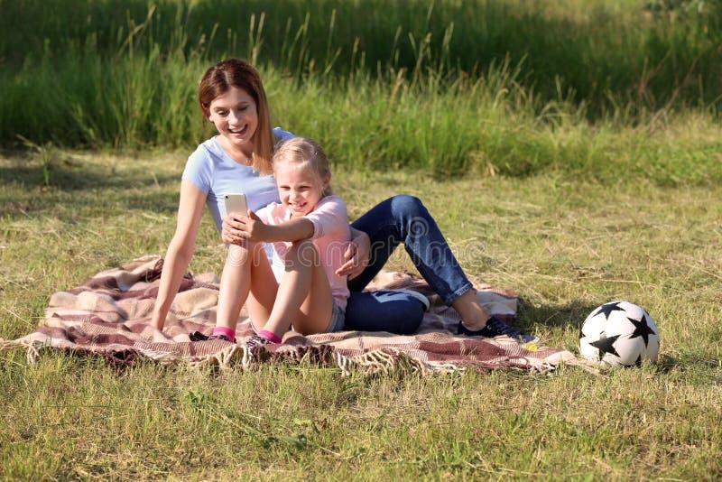 Mãe e sua filha pequena que tomam o selfie no parque fotos de stock