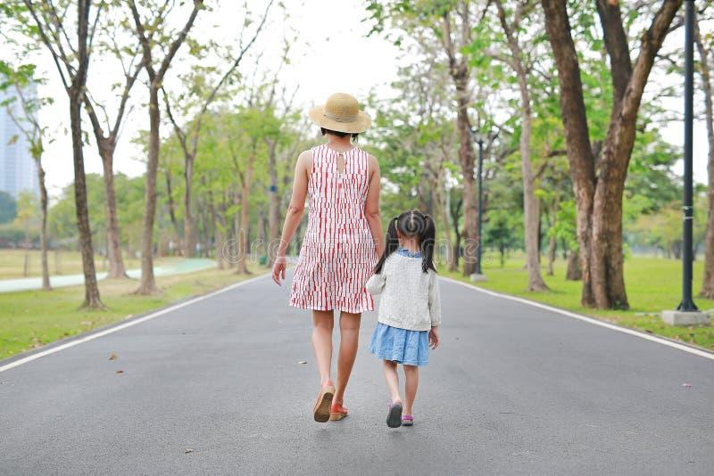 Mãe e sua filha que andam na estrada e que guardam as mãos no jardim exterior da natureza Vista traseira foto de stock royalty free