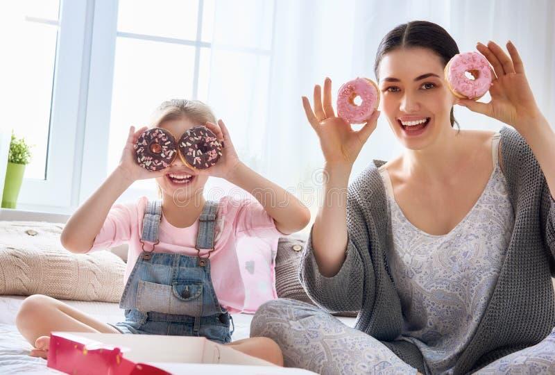 Mãe e sua filha que comem anéis de espuma imagens de stock royalty free