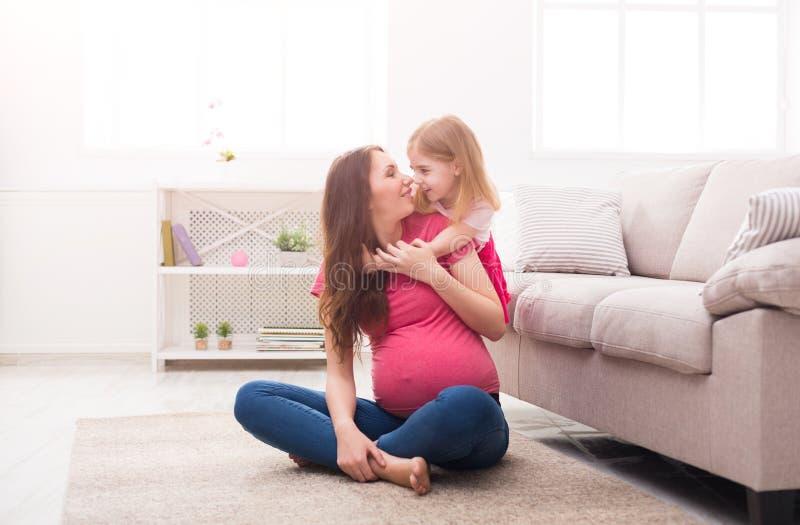 Mãe e sua filha que jogam e que abraçam imagem de stock