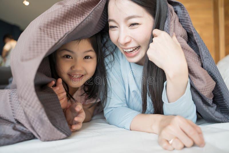 Mãe e sua menina da criança da filha que jogam no quarto e que põem a cobertura sobre Fam?lia asi?tica feliz fotografia de stock royalty free