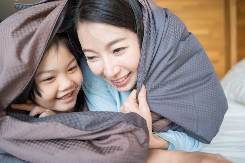 Mãe e sua menina da criança da filha que jogam no quarto e que põem a cobertura sobre Fam?lia asi?tica feliz foto de stock royalty free