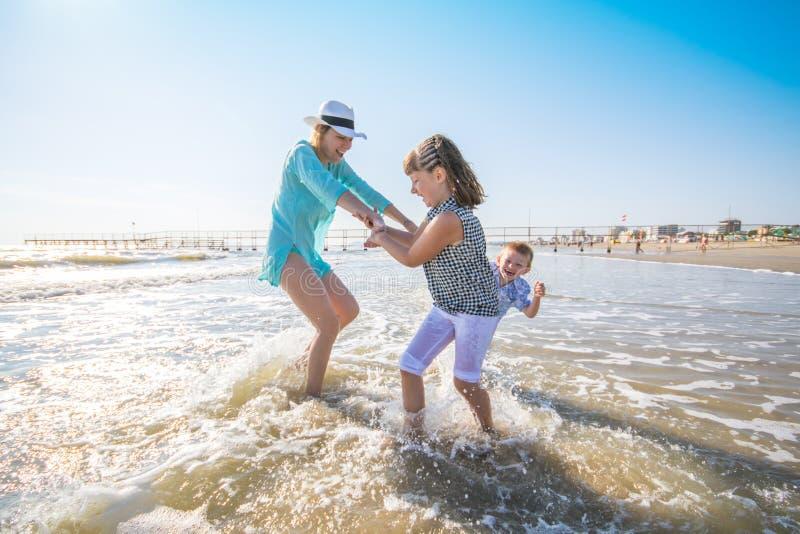 Mãe e suas crianças que jogam no mar imagem de stock