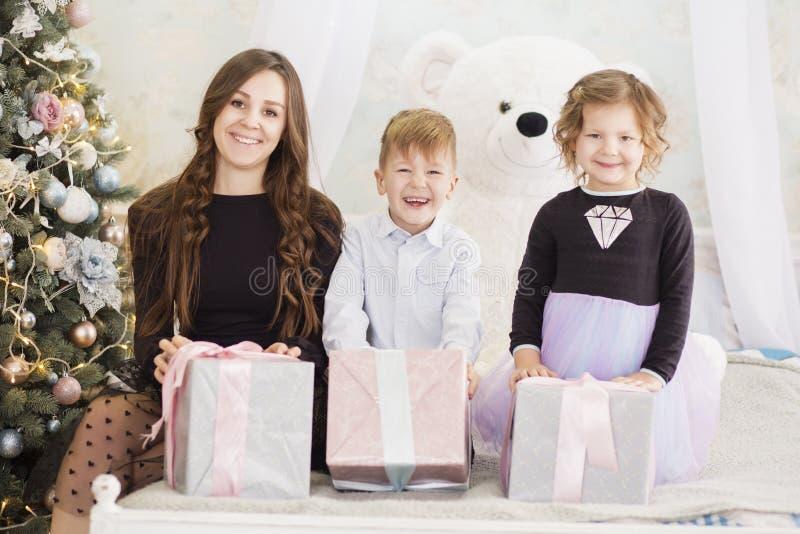 M?e e suas duas crian?as pequenas com caixas de presente do Natal Fam?lia na Noite de Natal M?e e crian?as que abrem o Xmas foto de stock royalty free