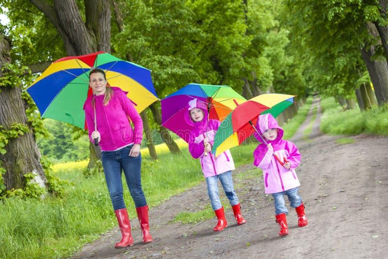 Mãe e suas filhas com guarda-chuvas imagem de stock