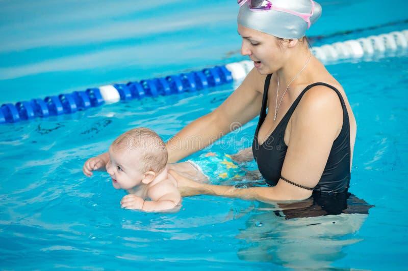 A mãe ensina seu bebê, como nadar em uma piscina fotografia de stock royalty free