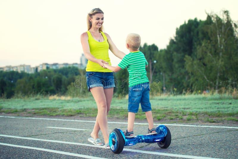 A mãe ensina seu filho pequeno montar na placa do equilíbrio fotos de stock