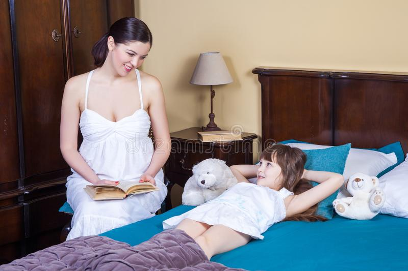 A mãe ensina sua filha ler Os relacionamentos no meio paren fotografia de stock royalty free
