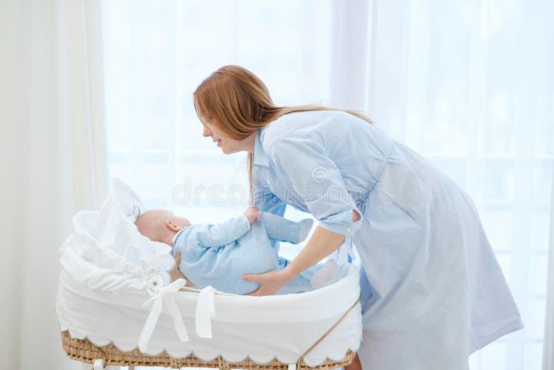 Mãe envelhecida média que põe seu bebê em um berço fotografia de stock royalty free